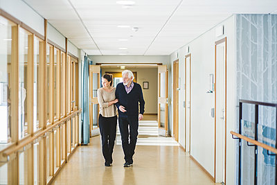 Young woman looking away while walking with grandfather in corridor at nursing home - p426m2018710 by Maskot