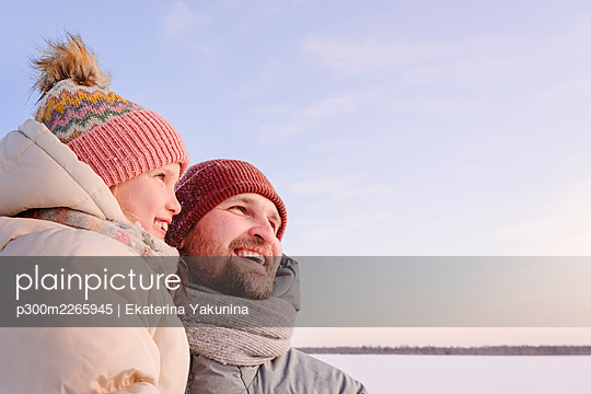 Father and daughter in warm clothing looking away during sunset - p300m2265945 by Ekaterina Yakunina