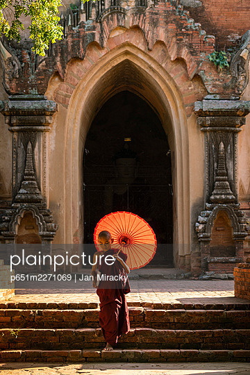Novice Buddhist monk with red umbrella walking away from temple, Bagan, Mandalay Region, Myanmar - p651m2271069 by Jan Miracky