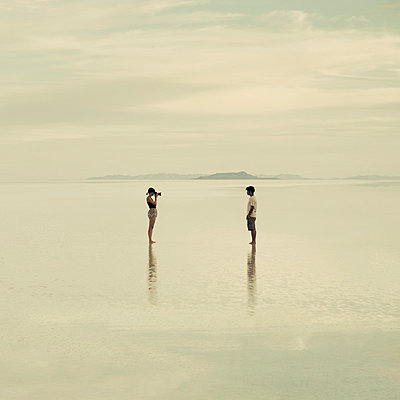 Man and woman standing on the flooded Bonneville Salt Flats, taking photographs of each other at dusk. - p1100m875904f by Paul Edmondson