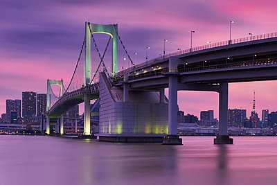 Rainbow bridge and Tokyo tower against sky during sunset - p1166m1530534 by Cavan Images