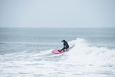 Man surfing during winter snow - p1166m2177123 by Cavan Images