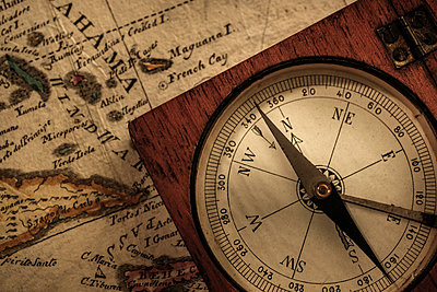 Antique compass on map - p1427m2124051 by Tetra Images