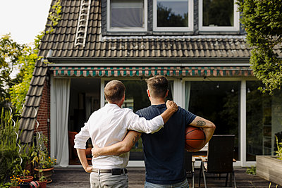 Father and son with arm around standing in front of house - p300m2276939 by Gustafsson
