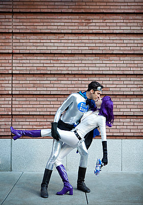 Couple in superhero costumes kissing - p555m1478354 by Kyle Monk