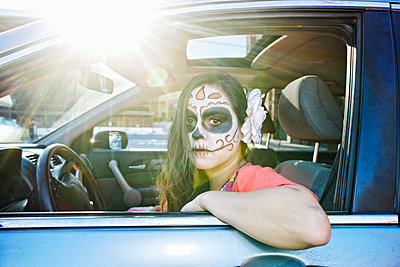 Hispanic woman driving car wearing skull face paint - p555m1491011 by Peathegee Inc