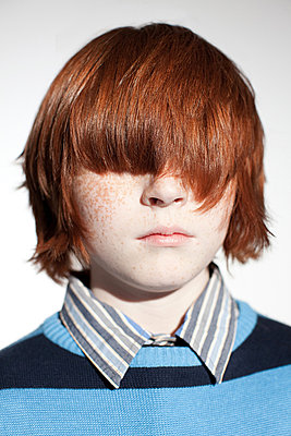 Boy with hair covering his eyes - p9245699f by Image Source