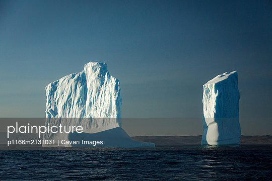 Iceberg toweres flaot off shore in the Torngat Mountains - p1166m2131031 by Cavan Images
