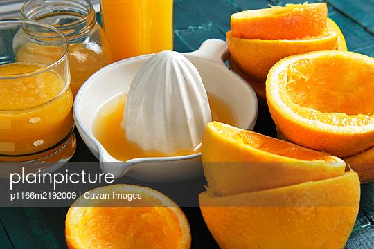 White ceramic juicer with orange peels and orange juice on a green woo - p1166m2192009 by Cavan Images