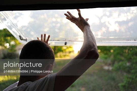 Jugendlicher blickt aus dem Fenster im Wohnwagen - p1468m1584994 von Philippe Leroux