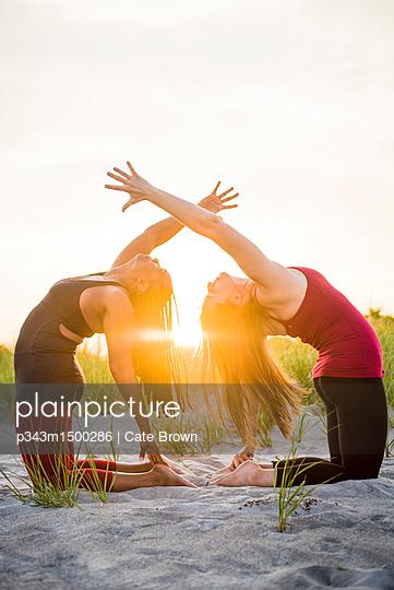 Two women doing yoga in Camel Pose (Ustrasana variation), Newport, Rhode Island, USA