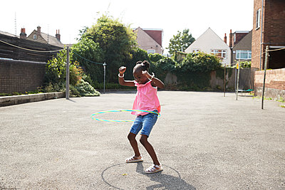 Playful happy girl spinning in plastic hoop in sunny neighborhood - p1023m2238497 by Himalayan Pics