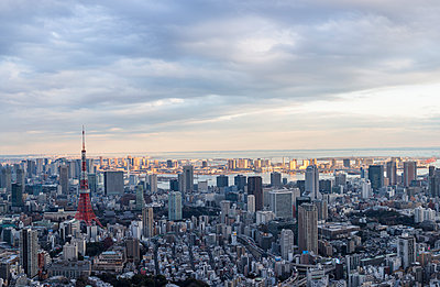Aerial view of Tokyo Tower amidst city against cloudy sky - p1166m1561539 by Cavan Images