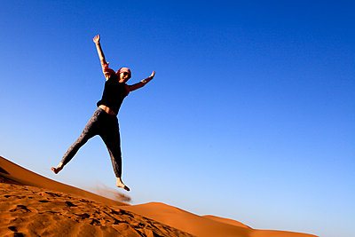 Woman jumping in the desert - p503m2064075 by Fabrice Arfaras