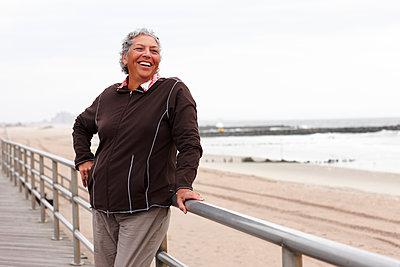 Smiling woman enjoying boardwalk - p555m1480044 by Granger Wootz