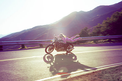 Man wearing pink onesie riding motorcycle, Malibu Canyon, California, USA - p924m1422757 by Raphye Alexius
