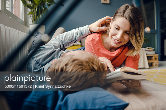 Happy couple reading and cuddling at home - p300m1581372 von Kniel Synnatzschke