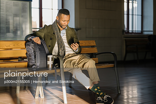 Stylish man using smartphone while sitting on a bench in a train station - p300m2155305 by Hernandez and Sorokina