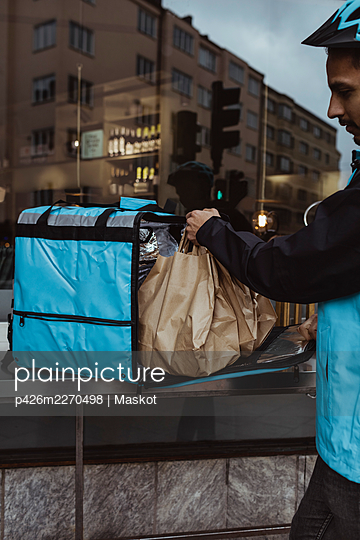Cropped image of delivery man putting package order in backpack outside store - p426m2270498 by Maskot