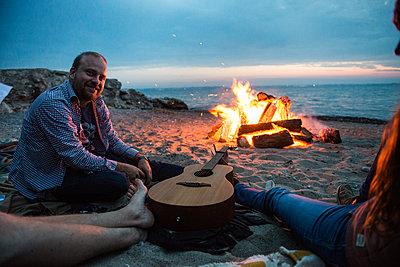 Freunde am Lagerfeuer am Strand - p1142m1362257 von Runar Lind