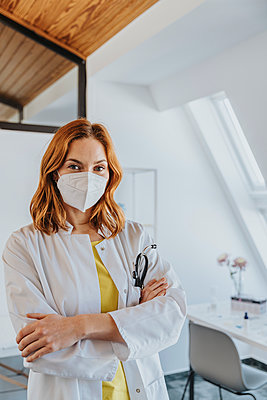Female doctor wearing protective face mask standing with arms crossed at clinic - p300m2266888 by Mareen Fischinger