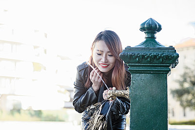 Young woman at drinking fountain, Milan, Italy - p429m1407841 by Costantino Costa