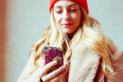 Junge Frau schaut zufrieden auf ihr Handy - p432m1502405 von mia takahara