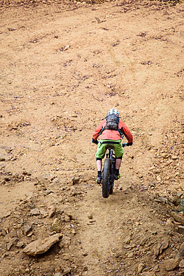 Caucasian man descending dirt trail on bicycle - p555m1491077 by Kolostock