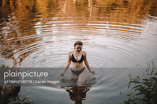 Young woman in a bikini walking in lake - p1166m2130716 by Cavan Images