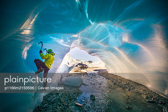 Man ice climbing in cave during luxury adventure tour. - p1166m2159596 by Cavan Images