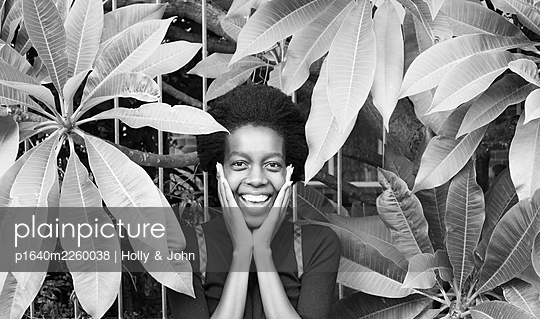 African woman between leaves, portrait - p1640m2260038 by Holly & John