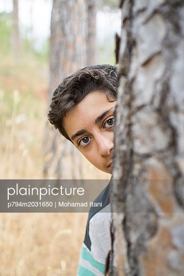 Ängstlicher Junge versteckt sich hinter einem Baum - p794m2031650 von Mohamad Itani
