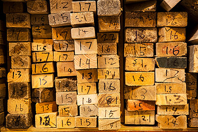 Close up of large selection of wooden planks stacked on shelves in a warehouse. - p1100m1575729 by Mint Images