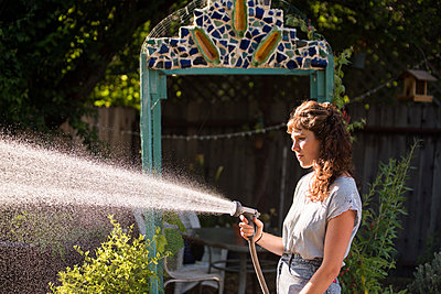 Side view of woman watering in garden using hose pipe - p1166m1541844 by Cavan Social