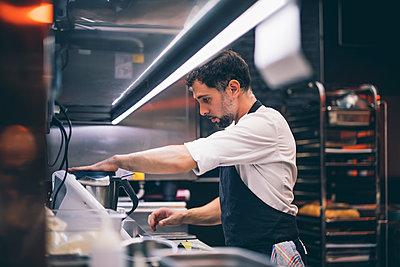 Cook at work in a restaurant kitchen - p300m2144258 von Oscar Carrascosa Martinez