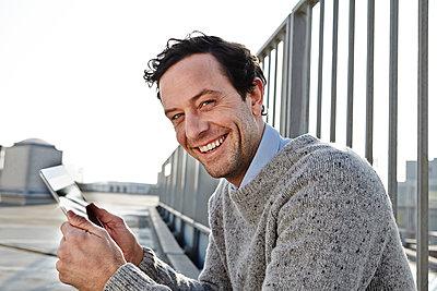 Portrait of smiling man holding tablet computer - p300m2213754 by Jo Kirchherr