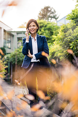 Smiling businesswoman talking on smart phone in office park - p300m2266671 by Joseffson