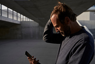 Mature businessman with hand in hair using mobile phone while standing under bridge - p300m2287277 by Stefanie Aumiller