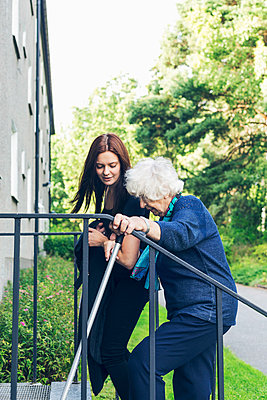 Young woman helping grandmother to climb steps outdoors - p426m1151726 by Maskot