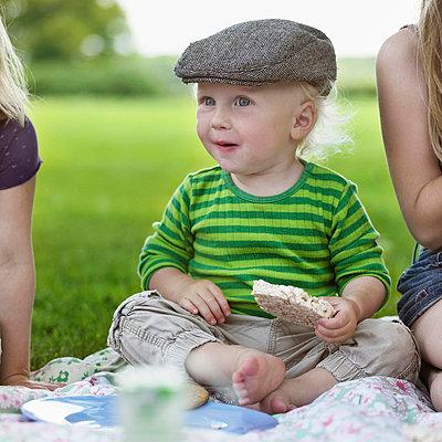 Boy eating rice cake at picnic - p42916711f by Henrik Weis
