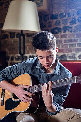Boy playing guitar - p940m1132357 by Bénédite Topuz