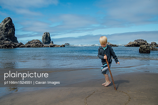 Boy making circle on sand with stick at beach - p1166m1524551 by Cavan Images