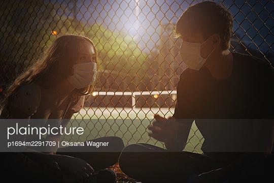 Junges Paar mit Masken an einem Sportplatz - p1694m2291709 von Oksana Wagner