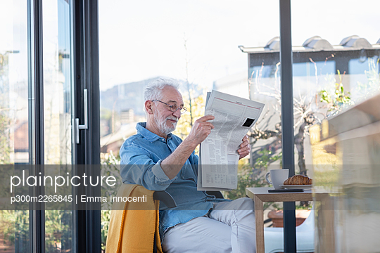 Man reading newspaper while sitting at home - p300m2265845 by Emma Innocenti