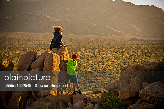 Boys standing on rocks admiring desert landscape - p555m1532549 by Stephen Simpson Inc