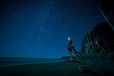 Hiker wearing headlamp sitting on tree trunk at La Push beach against star field - p1166m1485233 by Cavan Images