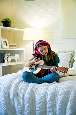 Teenage girl listening music through smart phone while sitting with guitar in bedroom - p1166m1489039 by Cavan Images