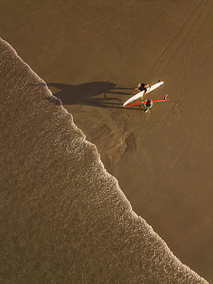 Aerial view of surfers at the beach - p1166m2137115 by Cavan Images