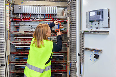 Female electrician working with voltmeter at fuse box - p300m2180854 by Zeljko Dangubic