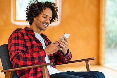 Young man using smart phone while sitting on armchair at spacious room - p300m2268019 by Steve Brookland